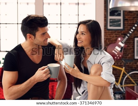 Happy young loving couple sitting at home, drinking tea, smiling. - stock photo