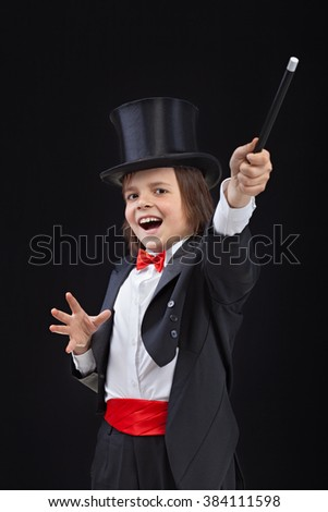 Happy young magician performing a trick with wide gestures - on dark background - stock photo
