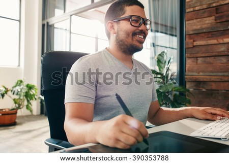 Happy young male designer working on graphics tablet using a stylus. Artist using new technology for editing his artwork. - stock photo