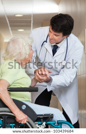 Happy young male doctor comforting senior patient at hospital