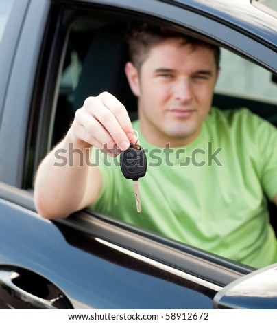 Happy young male driver sitting in blue car and holding his car key