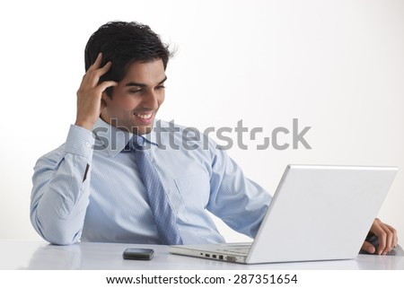 Happy young male executive smiling while looking at laptop - stock photo
