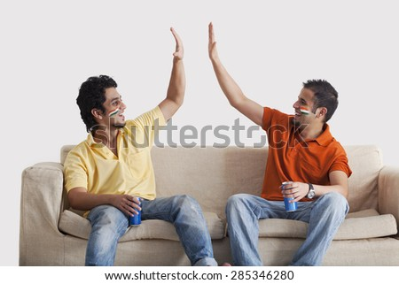 Happy young male friends in casuals giving a high-five to each other while holding tin cans - stock photo