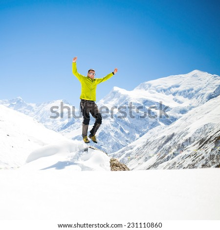 Happy young male hiker jumping in white winter mountains Himalayas.  Success climbing on snow, beautiful inspirational landscape with Annapurna peak in background and clear blue sky - stock photo