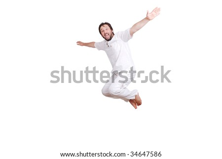 Happy young male in white clothes is jumping isolated - stock photo