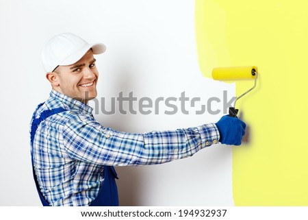 Happy young male painter painting a wall