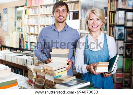 Happy young man and mature woman holding books in hands in book store