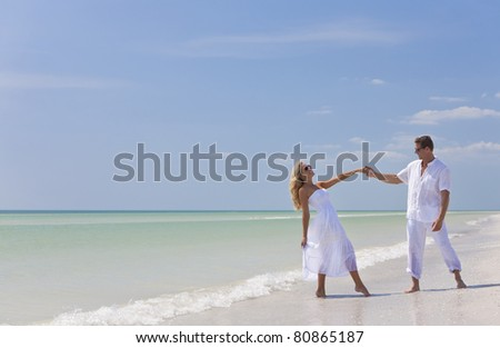 Happy young man and woman couple dancing and holding hands on a deserted tropical beach with bright clear blue sky