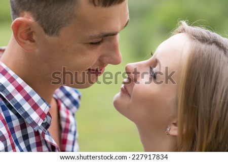 Happy young man and woman looking at each other against a background of trees