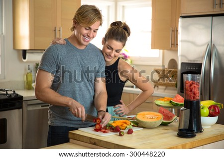 Happy young man and woman prepare a healthy recipe raw vegan lifestyle blonde handsome - stock photo