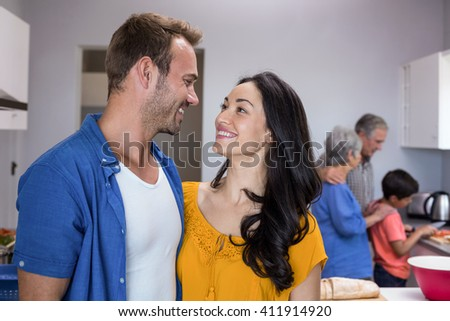 Happy young man and young woman standing in kitchen looking face to face - stock photo