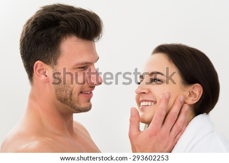 Happy Young Man Applying Moisturizer On Woman's Cheek Over White Background