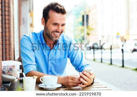 Happy young man browsing internet on smartphone sitting at outdoor cafe. - stock photo