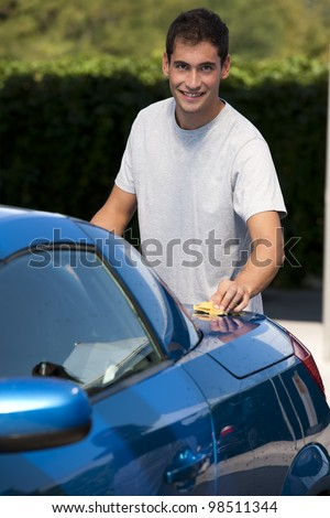 Happy young man cleaning his car with sponge - stock photo