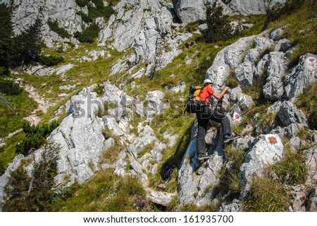 happy young man climbing a rocky passage while exploring the wilderness - stock photo