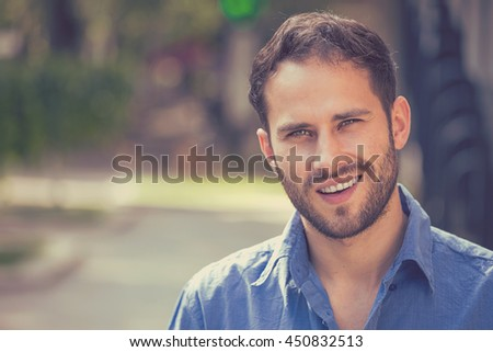 Happy young man. Closeup portrait of handsome guy in casual shirt smiling while standing against city urban background