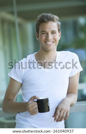 Happy young man drinking coffee