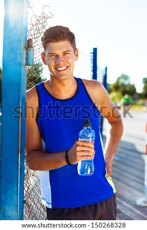 Happy young man drinking water after workout - stock photo