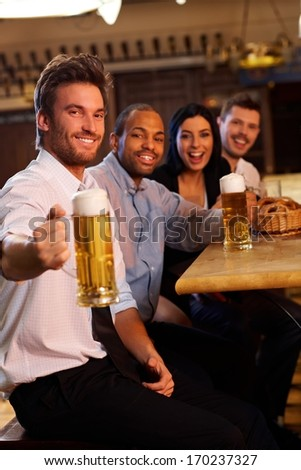 Happy young man drinking with friends in pub. Holding mug of beer, looking at camera, smiling.