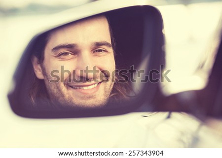 Happy young man driver looking in car side view mirror, making sure line is free before making a turn. Positive human face expression emotions. Safe trip journey driving concept - stock photo