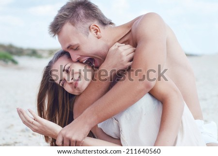 happy young man embracing smiling young woman and shouting loud on a summer beach - stock photo