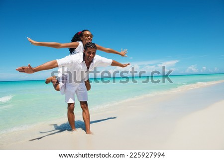Happy , young man giving a piggy back to his girlfriend at the tropical beach.Copy space - stock photo