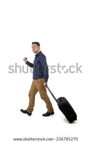 Happy young man going on a vacation while holding his suitcase against a white background - stock photo