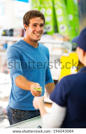 happy young man handing over credit card to a female cashier at till point - stock photo