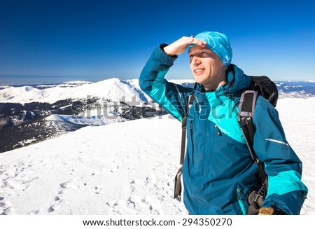 Happy young man hiking on mountain in winter