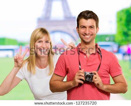 Happy Young Man Holding Camera In Front Of Woman Gesturing, Outdoor - stock photo