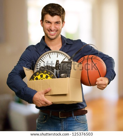 Happy Young Man Holding Card boxes Gesturing, Indoor