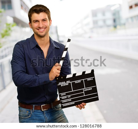 Happy Young Man Holding Clapboard, Outdoor - stock photo