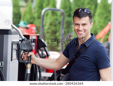 Happy young man holding fuel nozzle at gas station - stock photo