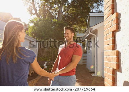 Happy young man holding hand of his girlfriend and walking around their house. Loving young couple outdoors in their backyard on a bright sunny day. - stock photo