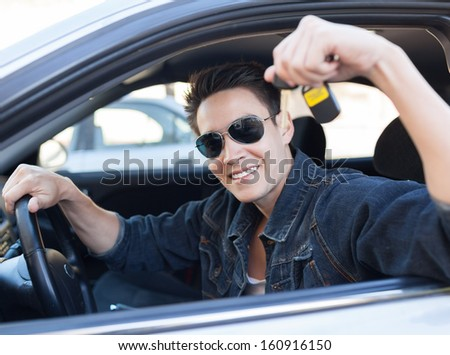 Happy young man holding keys to his new car  - stock photo
