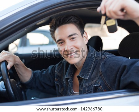 Happy young man holding keys to new car - stock photo