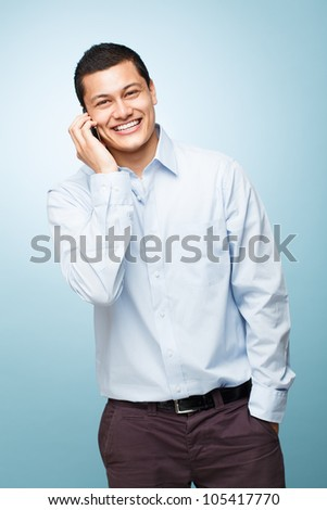 Happy young man holding mobile phone - stock photo