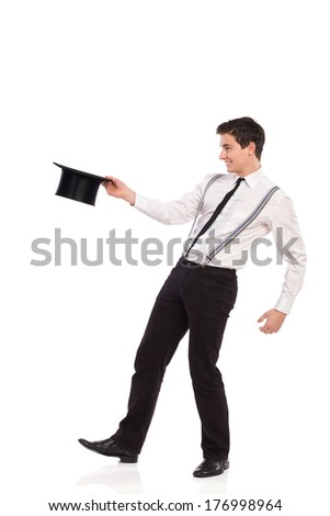 Happy young man holding top hat. Full length studio shot isolated on white. - stock photo