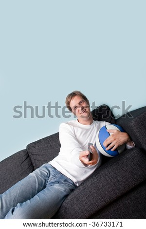 Happy young man holding tv remote and basket ball