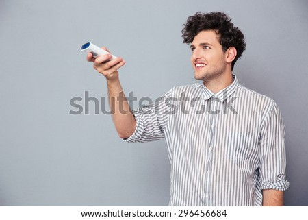 Happy young man holding TV remote over gray background - stock photo
