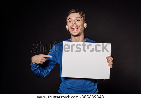 Happy young man holding white blank panel with space for text on black background. - stock photo