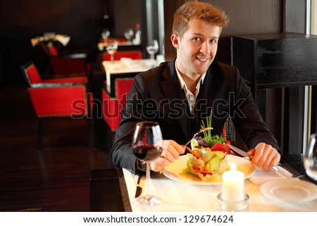 Happy young man in black suit in a restaurant - stock photo