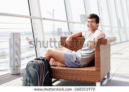 Happy young man in glasses and headphones sitting on chair in airport departure lounge - stock photo