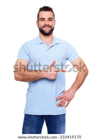Happy young man in polo shirt showing empty copyspace on white background - stock photo