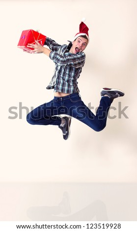 Happy young man in santa cap in hurry running or jumping with gifts - stock photo
