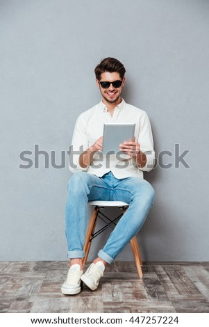 Happy young man in sunglasses sitting on chair and using tablet over grey background - stock photo