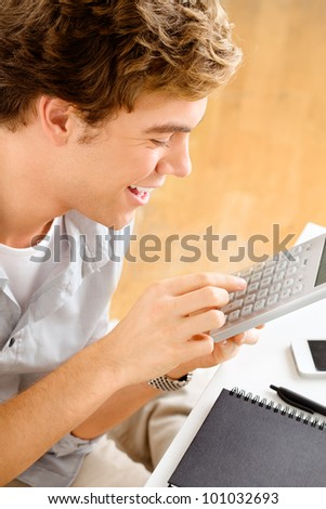 Happy young man is a student studying at home holding calculator