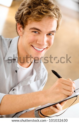 Happy young man is a student studying at home holding pen and sm - stock photo