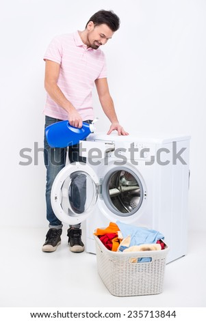 Happy young man is doing laundry at home, on the white background.