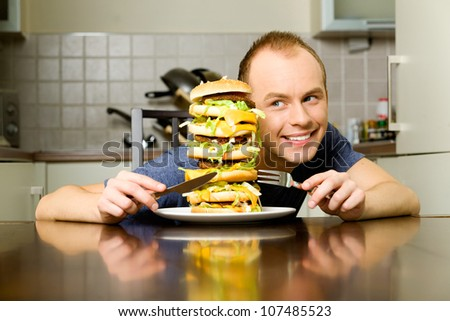 Happy young man is going to eat big layered cheeseburger